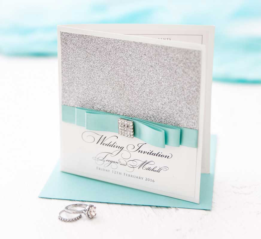 wedding invitation with aqua ribbon and silver glitter